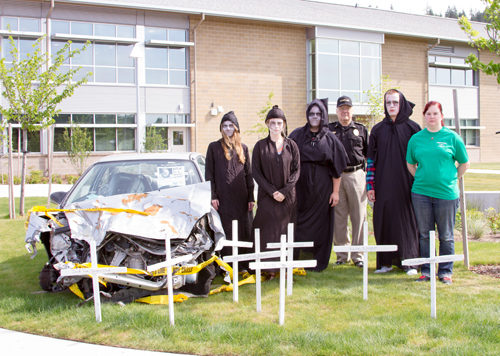 Participating students hammer white crosses with their names on them by a car involved in an actual drunk driving accident at the front of the school.