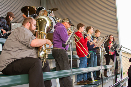 Dan Morrill (left, playing tuba) and Jim Bair (playing trombone) volunteer to help fill out the Woodland High School Pep Band's sound.