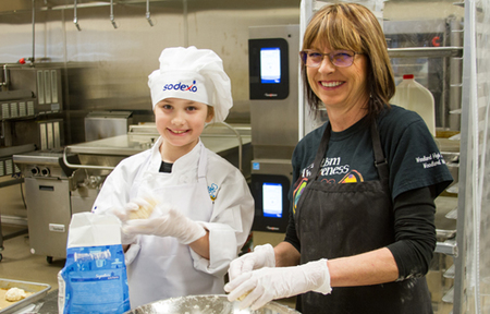 Keira Rhodes (left) prepares her gold-award winning comfort food - Biscuits and Gravy with Green Beans.
