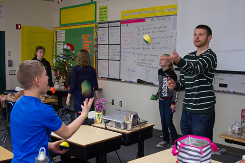 Tyler Thralls tosses a ball to a club member to teach how to juggle as a team.