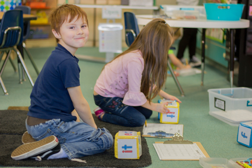 At one station, students toss blocks with different words and then select a word that rhymes with the one on their block.