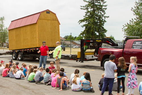 Nick Cutler demonstrated how his company uses special flatbed trailers to deliver large sheds to homes and businesses.